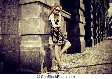 outdoor fashion - Beautiful fashionable woman standing on...