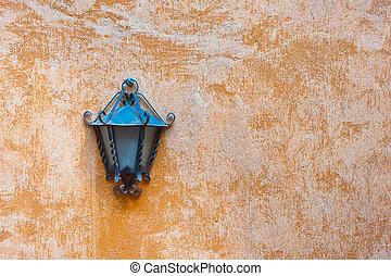 Outdoor garden lamp on orange wall