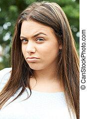 Outdoor Head And Shoulders Portrait Of Serious Teenage Girl