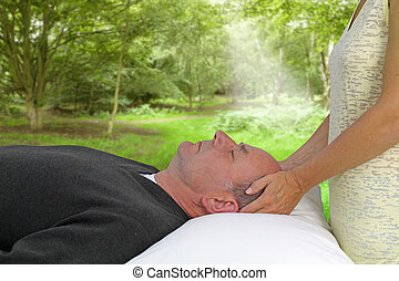 Female healer giving healing to male supine client outdoors with a woodland background