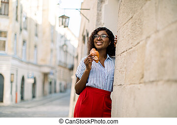 Outdoor horizontal shot of pretty African woman in striped shirt and red pants, enjoying her lunch time, posing with a croissant, leaning on the wall of vintage building in the city. Copy space