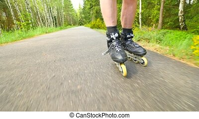Outdoor inline skating on smooth asphalt in the forest. Close up view to light skin man legs quick movement of inline boots.