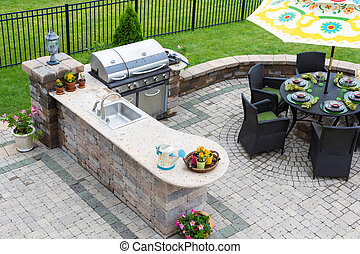 Outdoor kitchen and dining table on a paved patio - High...