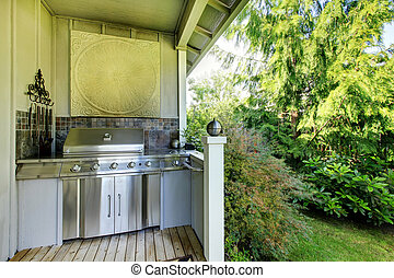 Outdoor kitchen area with zebra rug and plants.