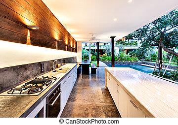 Outdoor kitchen with a stove an countertop next to garden...