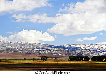 outdoor landscape with snow on mountains, blue sky
