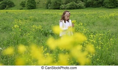 one little gilr in white clothes pick yellow flowers on summer green field
