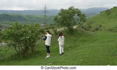 two little kids girls sisters in rural area among mountains and green grass and plants