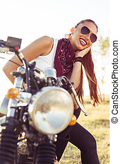 Outdoor lifestyle portrait of young biker woman sitting on a vintage custom motorcycle