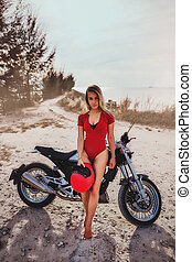 Outdoor lifestyle portrait of young sexy woman in red swimsuit sitting on a vintage custom motorcycle