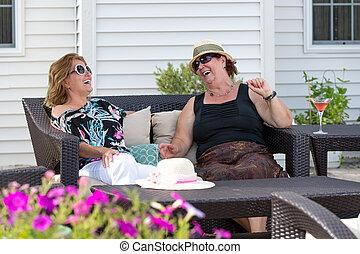 Outdoor Living Conversations - Couple women having happy...