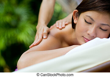 Outdoor Massage - A young woman having massage outside in...