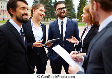 Outdoor meeting - Group of business people talking at...