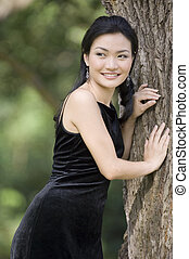 Outdoor Model 17 - A beautiful asian model poses leaning...