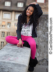 Outdoor of a portrait happy young african american teenage girl listening to music