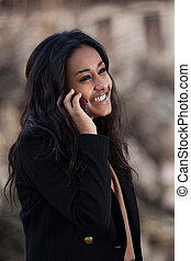 Outdoor of a portrait happy young black teenage girl using a mobile phone