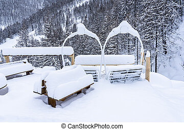 Outdoor picnic table and chairs covered in a thick layer of untouched deep snow. Snow-covered park on the mountains.