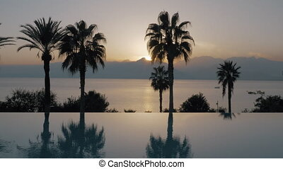 Outdoor pool on resort and nature landscape at sunset,...