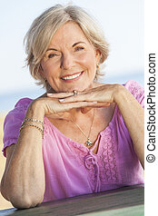 Outdoor portrait of an attractive elegant classy senior woman happy & smiling