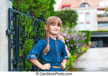 Outdoor portrait of a beautiful little girl wearing jeans dress, standing next to gate, with house on background