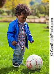 Outdoor portrait of a black baby playing soccer