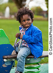 Outdoor portrait of a black baby  playing at playground