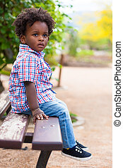 Outdoor portrait of a black little boy sited on a bench