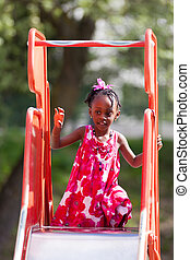 Outdoor Portrait of a cute african american little girl playing at playground