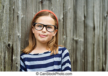 Outdoor portrait of a cute little 9 year old girl wearing...