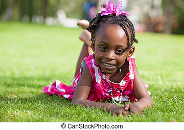 Outdoor portrait  of a cute little African american girl lying down on the grass