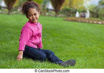 Outdoor portrait of a cute little African Asian girl lying seated on the grass