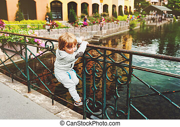 Outdoor portrait of a cute little blond boy looking at beautiful canal in Annecy, France. Travel with kids