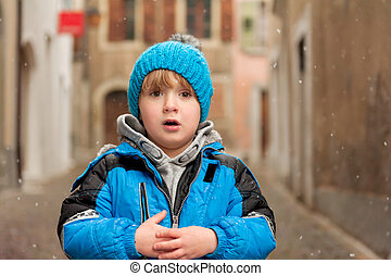 Outdoor portrait of a cute little boy in a city under snowfall, wearing warm blue jacket and knitted hat