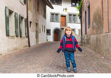Outdoor portrait of a cute little boy in an old town