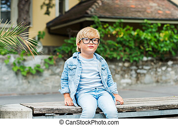 Outdoor portrait of a cute little boy in glasses