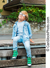Outdoor portrait of a cute little boy in glasses, wearing denim clothes and green shoes