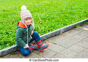 Outdoor portrait of a cute little boy of 3 years old, wearing warm coat, hat and boots