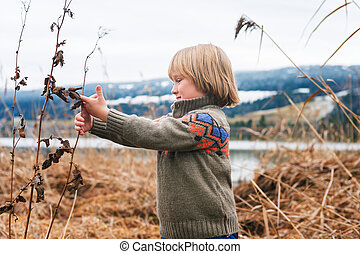 Outdoor portrait of a cute little boy of 4-5 years old, playing by the lake on a cold day