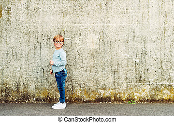 Outdoor portrait of a cute little boy wearing eyeglasses, light blue pullover and denim jeans. Back to school concept