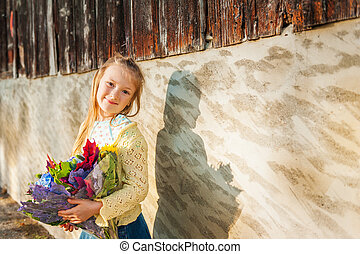 Outdoor portrait of a cute little girl holding beautiful bouquet of autumn flowers