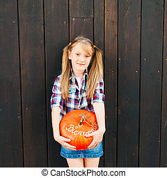 Outdoor portrait of a cute little girl holding big pumpkin with french sign Bienvenue (welcome)