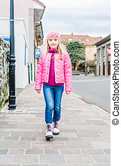 Outdoor portrait of a cute little girl in a city on a nice day
