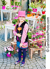 Outdoor portrait of a cute little girl in a city on a nice sunny day, standing next to flower shop, holding a beautiful rose