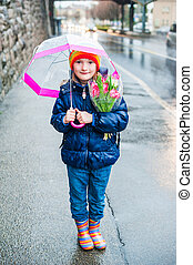 Outdoor portrait of a cute little girl in a city on a rainy day
