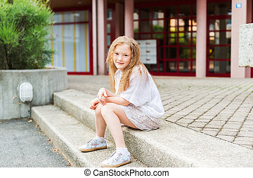 Outdoor portrait of a cute little girl in a city, wearing white pullover