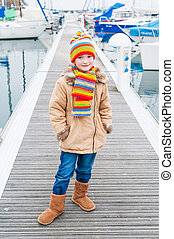 Outdoor portrait of a cute little girl in a colorful hat and scarf