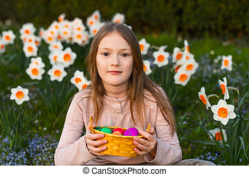 Outdoor portrait of a cute little girl in a spring garden, holding small bascket with colorful easter eggs