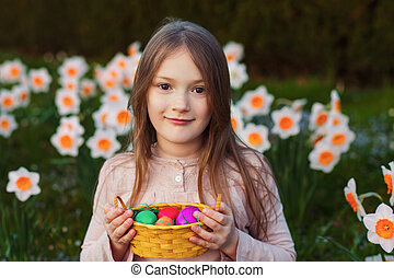 Outdoor portrait of a cute little girl in a spring garden, holding small basket with colorful easter eggs
