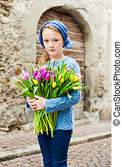Outdoor portrait of a cute little girl in an old city with huge bouquet of colorful fresh tulips