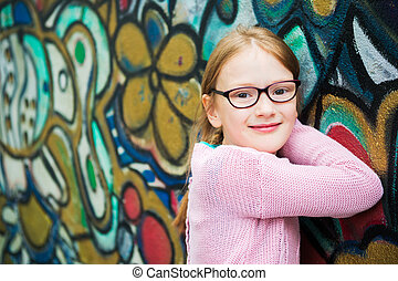 Outdoor portrait of a cute little girl in glasses